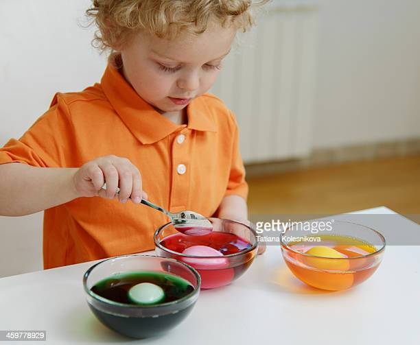 Child painting dyeing easter eggs