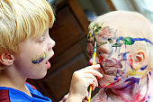 a Small child is painting the face of his baby brother, with colorful rainbow colors