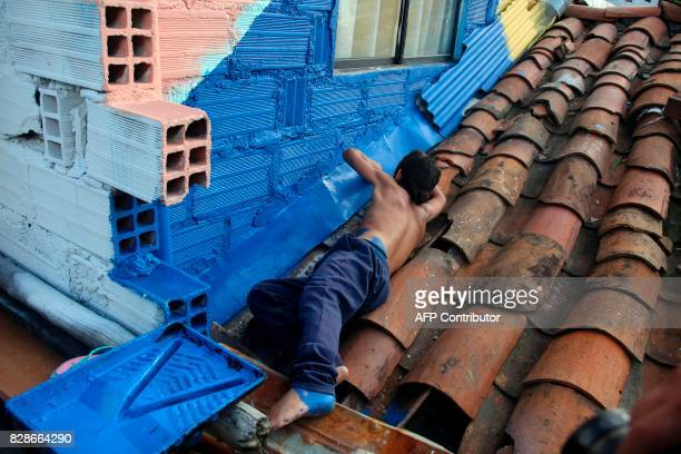A child paints a wall at El Pesebre shantytown in the outskirts of Medellin Colombia on June 30 2017 French artist Tarik Bouanani turned 230 brick...