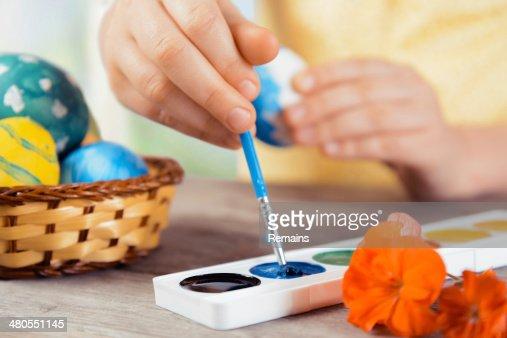 Niño pintura huevo de pascua en color azul : Foto de stock