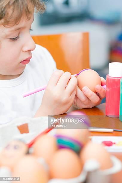 Child paints Easter eggs
