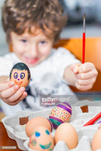 Child paints Easter eggs