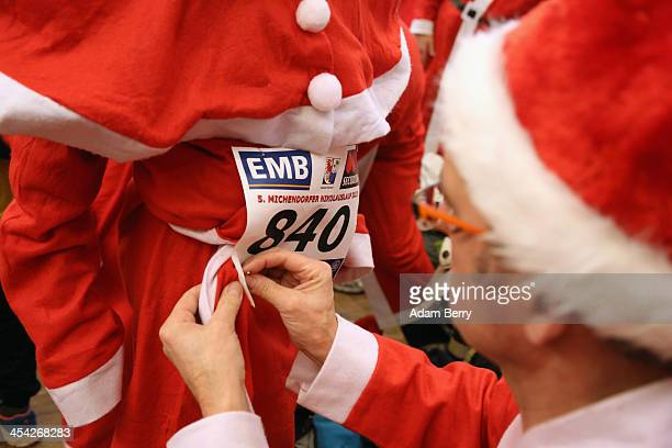 A child participant receives assistance in pinning on his number for 5th annual Michendorf Santa Run on December 8 2013 in Michendorf Germany Over...