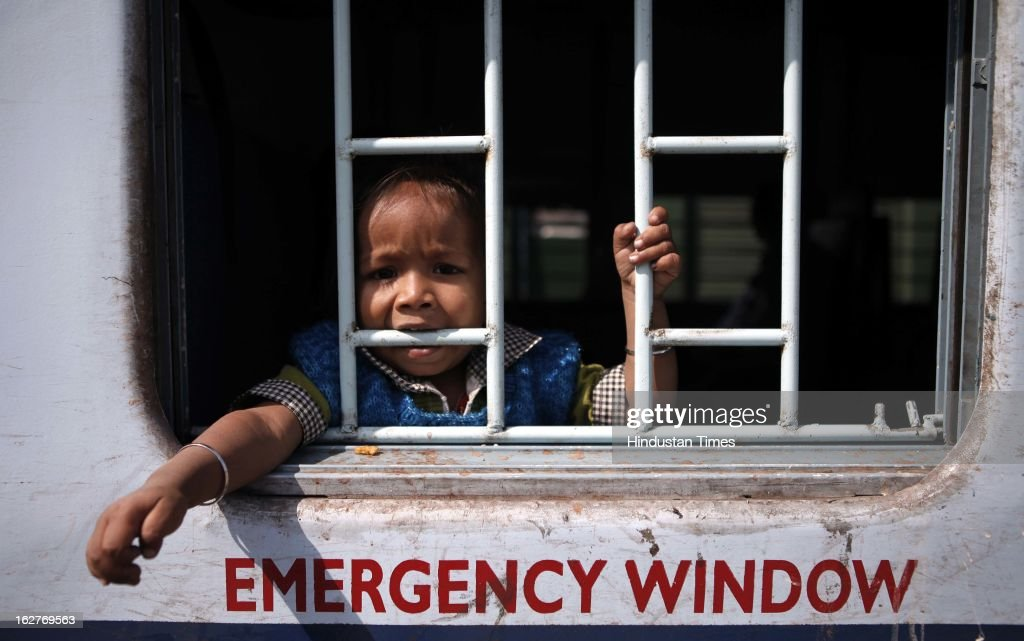 A child passenger biting the grill of a train at Nizamuddin railway station on February 26, 2013 in New Delhi, India. Indian Railway Minister Pawan Kumar Bansal presented his maiden Railway budget for the next fiscal year in the parliament.