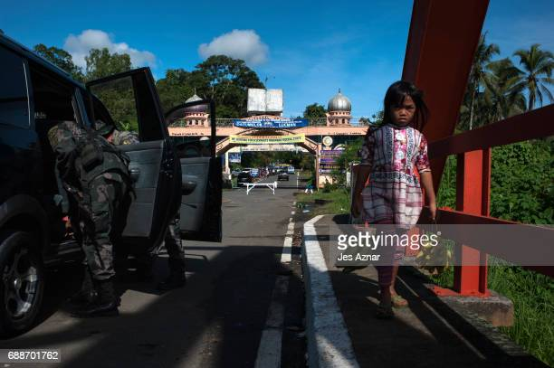 A child passes by armed security personel inspecting vehicles on the main highway on May 26 2017 in Marawi city southern Philippines Filipino...