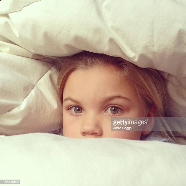 Child peeking out of fluffy white duvet