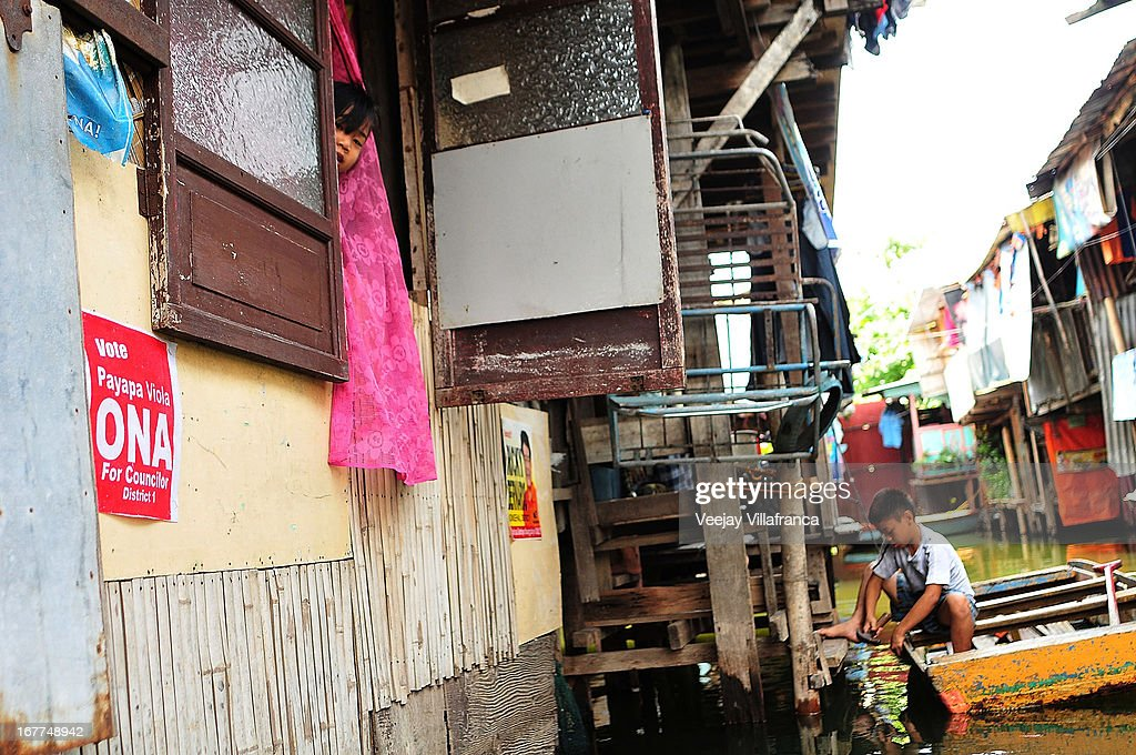 A child peeks through the window along the flooded waterways of Artex Compound in Malabon City on April 28, 2013 in Manila, Philippines. The residents of the former textile compound had to adjust their daily lives after flood waters submerged their low-lying village in 2004.