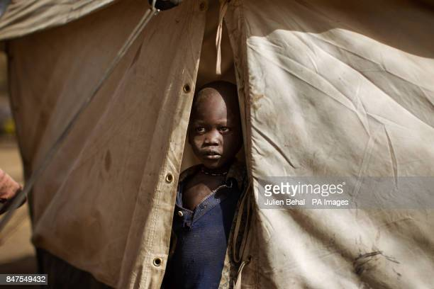A child peers out from his tent in Doro refugee camp in BunjMaban in the Upper Nile Blue Nile state of northeastern South Sudan AfricaThe region...