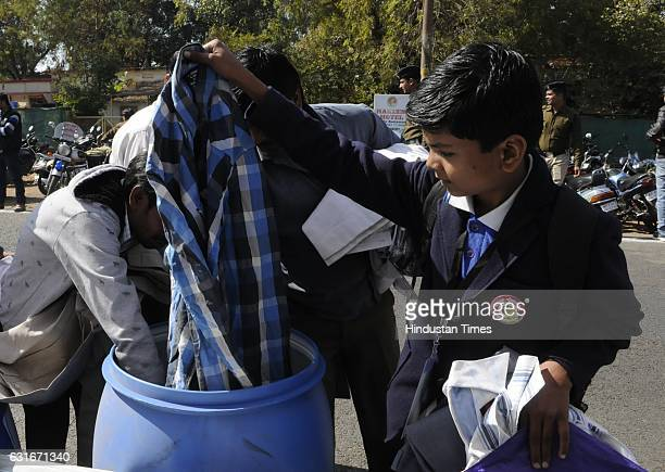 A child pick up clothes for his father from a collection box installed during an inauguration of weeklong programme of Happiness Department 'Anandam'...