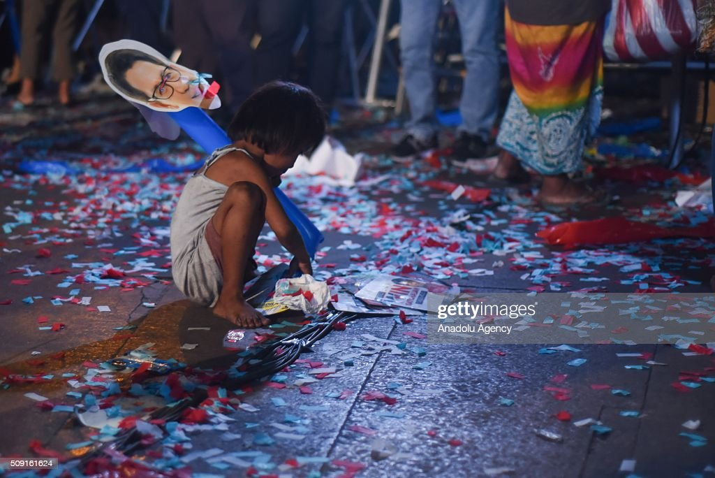 A child picks up election paraphernalia after a proclamation rally of presidential candidate Grace Poe-Llamanzares and vice presidential candidate Chiz Escudero at the Plaza Miranda in Manila on 09 February 2016. Poe-Llamanzaress candidacy was surrounded by controversy regarding her eligibility because of her US citizenship.