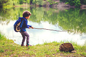 Little kid play with stick looks like rod and fishing on the lake in the forest on a sunny day.