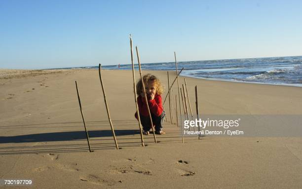 Child Playing Amidst Sticks At Beach Against Clear Sky