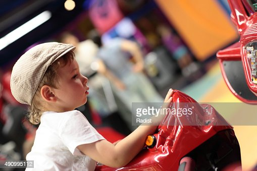 Child playing arcade simulator machine : Stock Photo