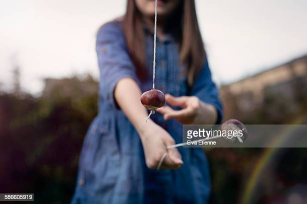 Child playing conkers with horse chestnut