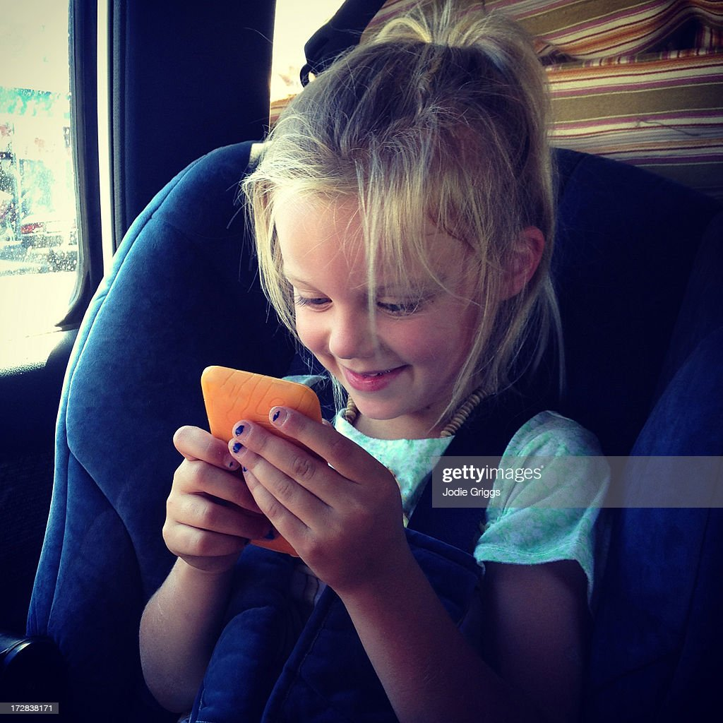 Child playing games on electronic device in car : Stock Photo