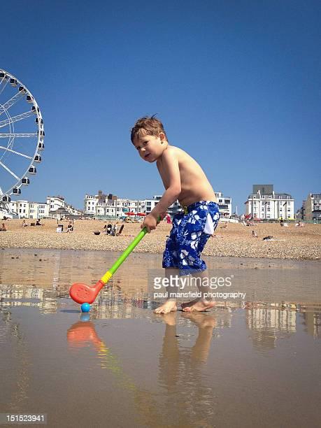 Child playing golf on beach