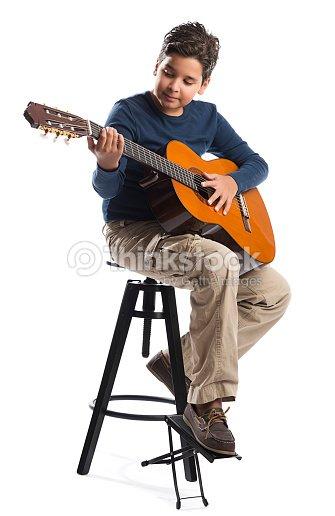 enfant jouant de la guitare sur une chaise photo thinkstock. Black Bedroom Furniture Sets. Home Design Ideas