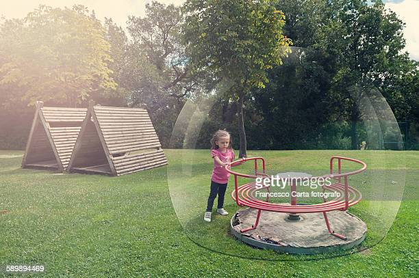 Child playing in a park inside a glass sphere