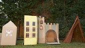 Child (4-5) playing in cardboard castle in garden