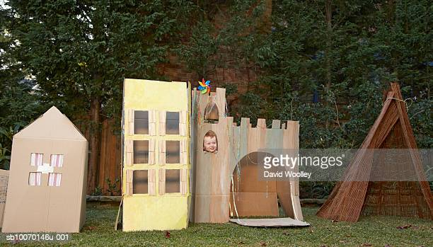 Child (4-5) playing in cardboard castle in garden