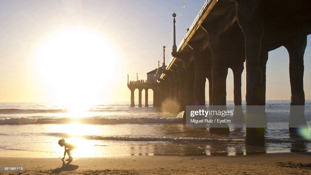Child Playing On Beach Beside Pier In Sea