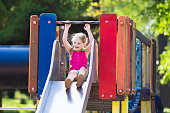 Child playing on outdoor playground in summer. Happy little girl having fun on swing and slide in school yard. Kids play outdoors. Preschooler swinging and climbing in kindergarten play center.