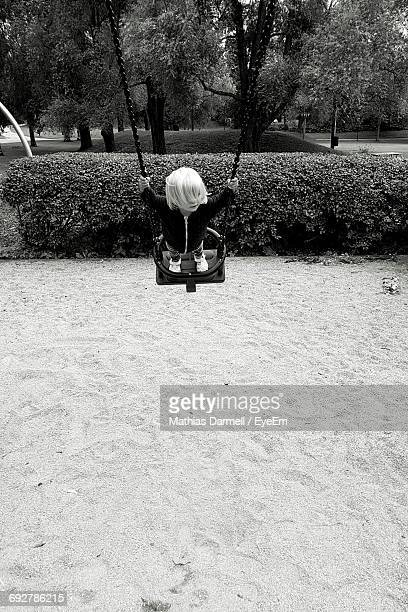 Child Playing On Swing In Park