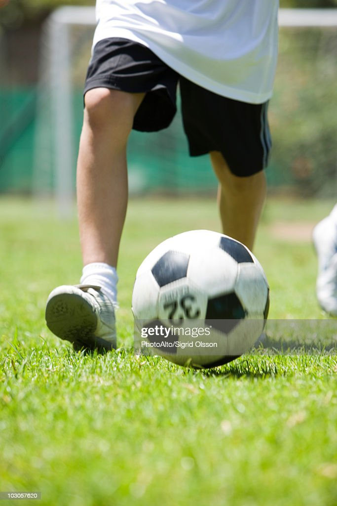 Child playing soccer, cropped : Stock Photo