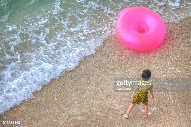A child playing with a recreational inner tube