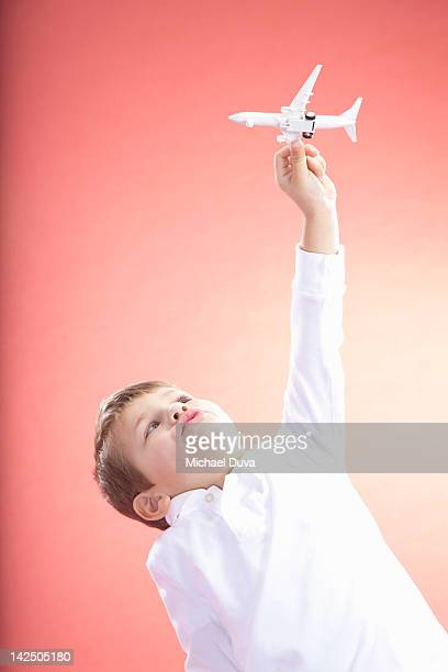 Child playing with airplane, imagining flight