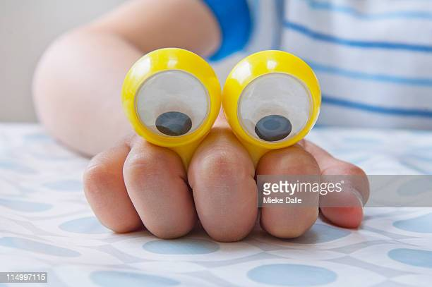 Child playing with cartoon eyes