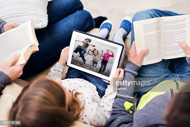 Child Playing With Digital Tablet Between Reading Parents
