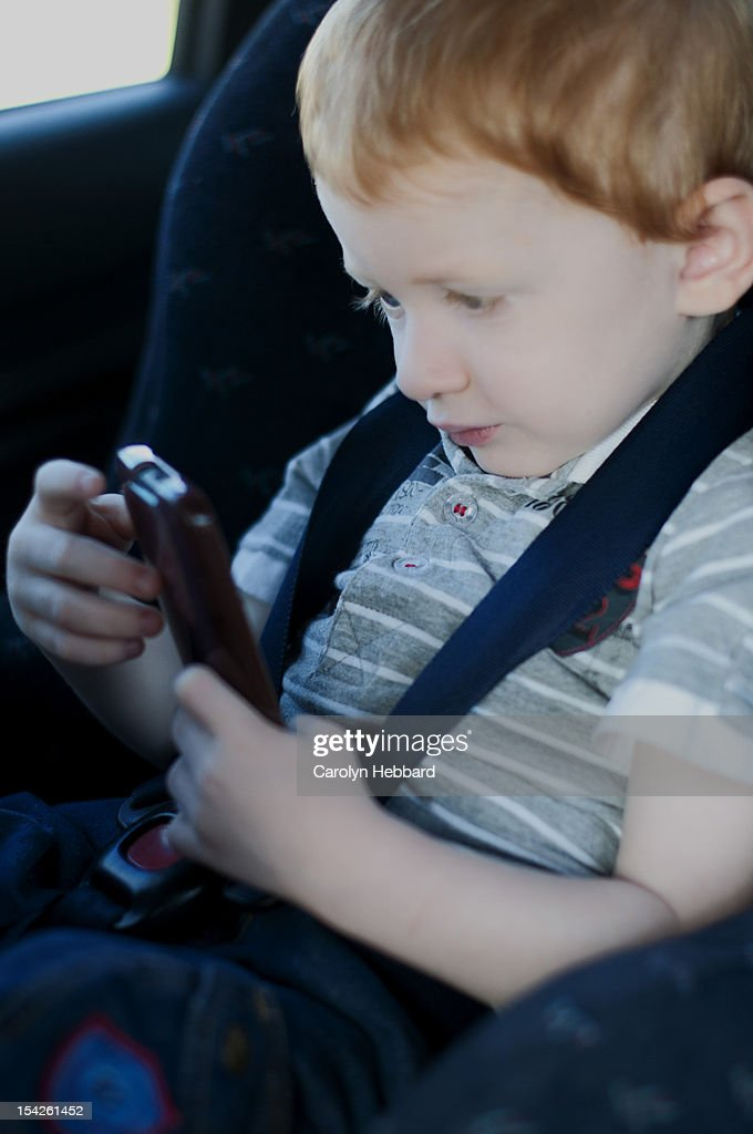 Child Playing with Phone in Car Seat : Stock Photo