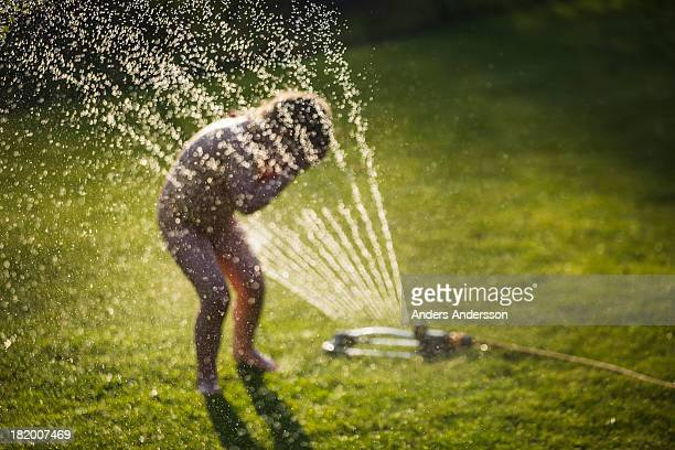 child playing with sprinkler
