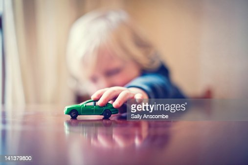 Child playing with toy car : Stock Photo
