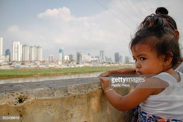 A child plays along the riverbank as high rise buildings are seen in the background