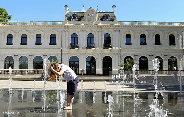 A child plays and freshens up on the water mirror in front of the theater of BrivelaGaillarde southwestern France on June 29 as a heatwave grips...