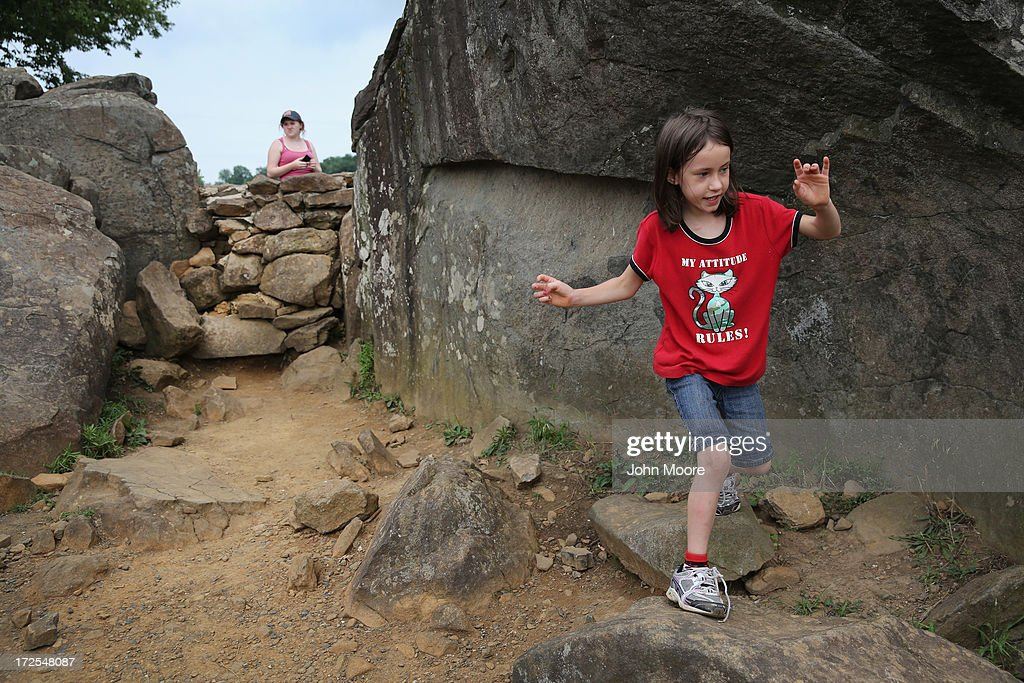 A child plays at Devil's Den on July 2, 2013 in Gettysburg, Pennsylvania, the 150th anniversary of the Battle of Gettysburg. Many tourists visiting the site pose for photos there as part of their battlefield experience. An historic photo entitled 'The Home of a Rebel Sharpshooter' was taken there by Alexander Gardner on July 5, 1863 and featured a dead Confederate soldier. The photograph was later discovered to be staged, the dead body of the 'sharpshooter' having been brought from another place on the battlefield for the photograph and the gun not a sharps rifle.