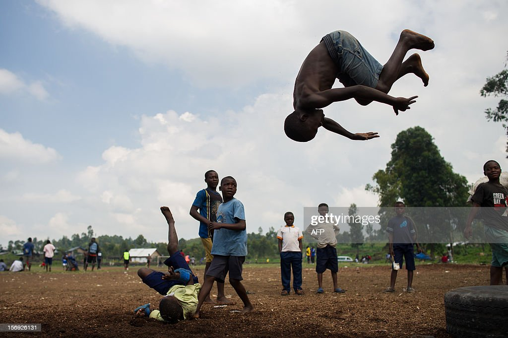 A child plays at gymnastics at the site of a settlement for internally displaced persons (IDPs) on the outskirts of Goma in the east of the Democratic Republic of the Congo on November 25, 2012. Over half a million people have been displaced in eastern Congo since the outbreak of the M23 rebellion. Diplomatic efforts continued on November 25 to resolve the crisis in eastern DR Congo, with an M23 rebel leader expected to hold further talks with President Joseph Kabila as the African Union called on the rebels to pull out from Goma. AFP PHOTO / PHIL MOORE