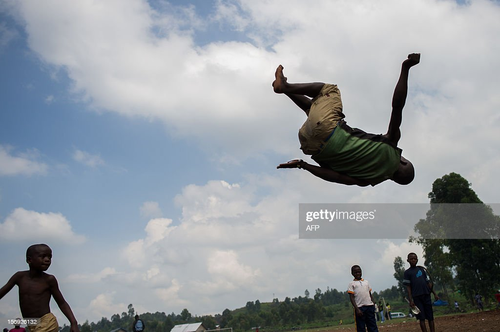 A child plays at gymnastics at the site of a settlement for internally displaced persons (IDPs) on the outskirts of Goma in the east of the Democratic Republic of the Congo on November 25, 2012. Over half a million people have been displaced in eastern Congo since the outbreak of the M23 rebellion. Diplomatic efforts continued on November 25 to resolve the crisis in eastern DR Congo, with an M23 rebel leader expected to hold further talks with President Joseph Kabila as the African Union called on the rebels to pull out from Goma.