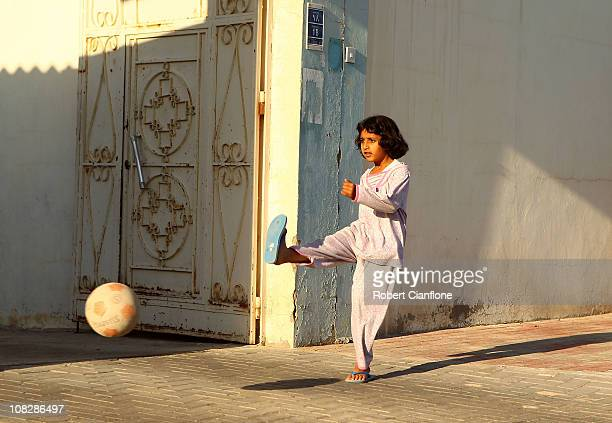 A child plays football on a local street in Doha on January 24 2011 in Doha Qatar