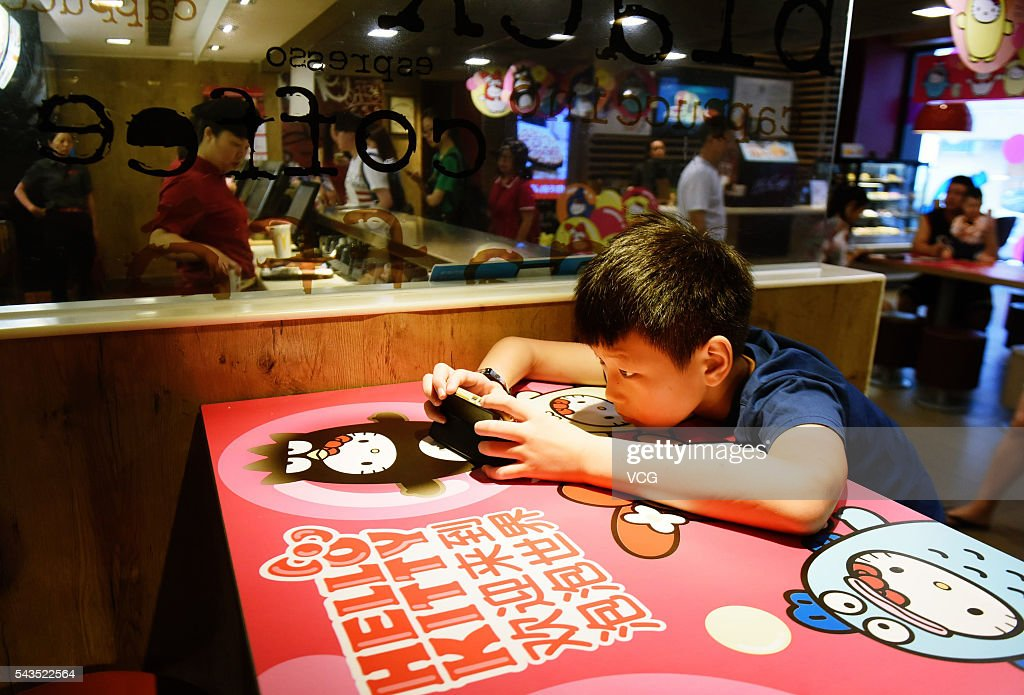 A child plays games on phone at a Hello Kitty theme restaurant on June 29, 2016 in Hangzhou, Zhejiang Province of China. A Hello Kitty theme restaurant was authorized opened firstly in Hangzhou.