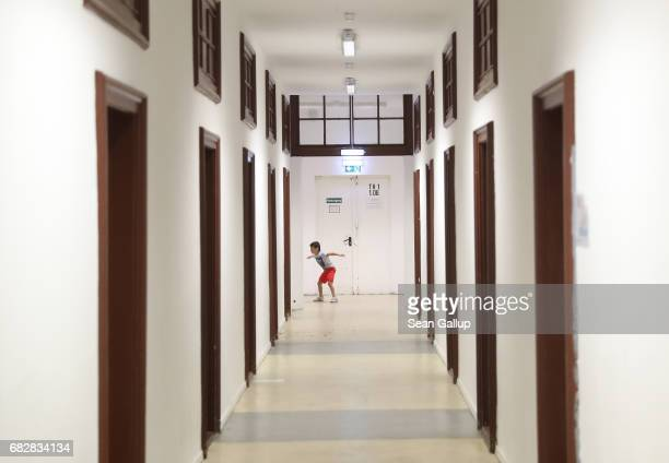 A child plays in a hallway outside the room where he and his family live at a shelter for refugees and migrants in Marienfelde district on May 3 2017...