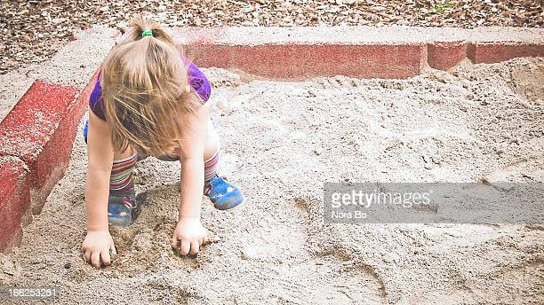 Child plays in a playground sand box