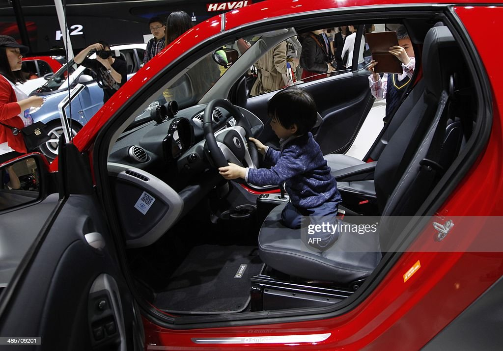 A child plays in a Smart car on display at the China International Exhibition Center new venue during the 'Auto China 2014' Beijing International Automotive Exhibition in Beijing on April 20, 2014. Leading automakers are gathering in Beijing for the kickoff of China's biggest car show, but lackluster growth and environmental restrictions in the world's largest car market have thrown uncertainty into the mix. More than 1,100 vehicles are being showcased at the auto show, which opens to the public on April 21. CHINA