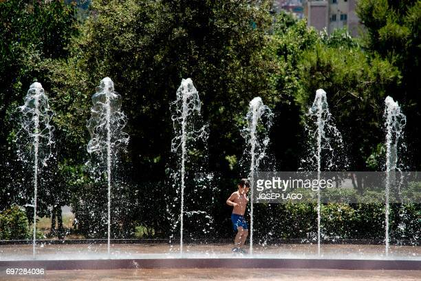 A child plays in fountains of Barcelona on June 18 to cool off as temperatures rose high across Spain Spain goes through a heatwave with temperatures...
