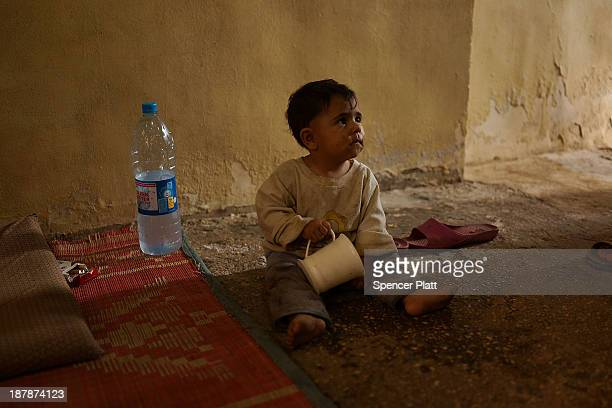A child plays in the room he shares with over 10 other Syrian refugees in an impoverished district of the city on November 13 2013 in Beirut Lebanon...