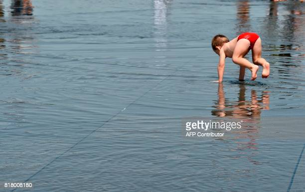 A child plays in the water of the 'Mirroir d'eau' a reflecting pool of water in Bordeaux where temperatures came close to 40 C on July 18 2017 / AFP...
