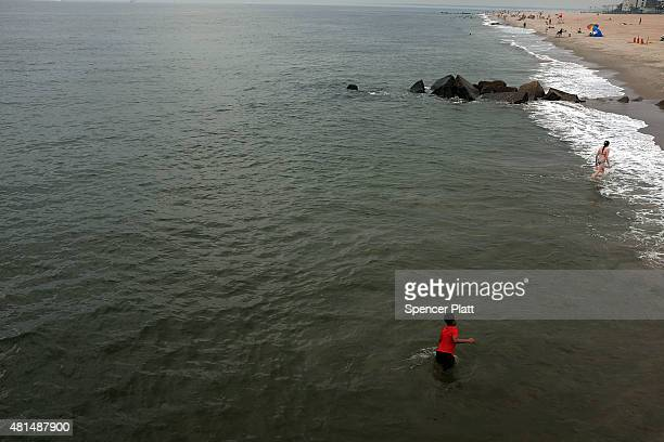 A child plays in the water on a sultry morning at Coney Island in Brooklyn on July 21 2015 in New York City Despite an overcast sky thousands of New...