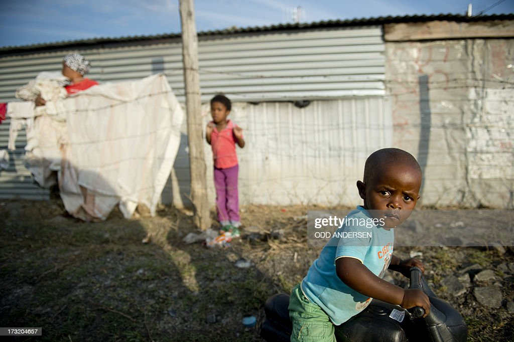 A child plays on a bicycle on July 9, 2013 in the Nkaneng shantytown next to the platinum mine, run by British company Lonmin, in Marikana. On August 16, 2012, police at the Marikana mine open fire on striking workers, killing 34 and injuring 78, during a strike was for better wages and living conditions. Miners still live in dire conditions despite a small wage increase.
